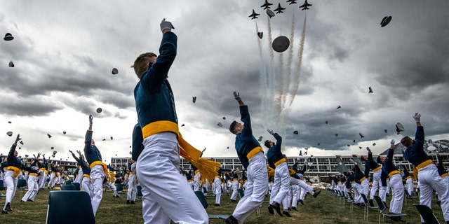 Spaced eight feet apart, United States Air Force Academy cadets celebrate their graduation as a team of F-16 Air Force Thunderbirds fly over the academy on April 18, 2020 in Colorado Springs, Colo. (Photo by Michael Ciaglo/Getty Images)