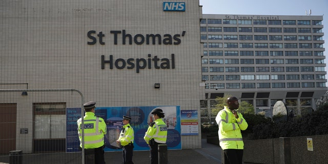 Three police officers at left and a security guard at right guard an entrance outside St Thomas' Hospital in London, where British Prime Minister Boris Johnson was being treated for coronavirus.