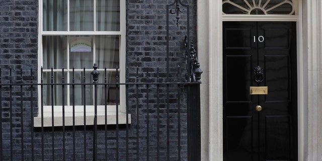 """A drawing of a rainbow with the words """"we are in this together"""" is displayed in one of the windows of 10 Downing Street in London, Thursday, April 9, 2020."""