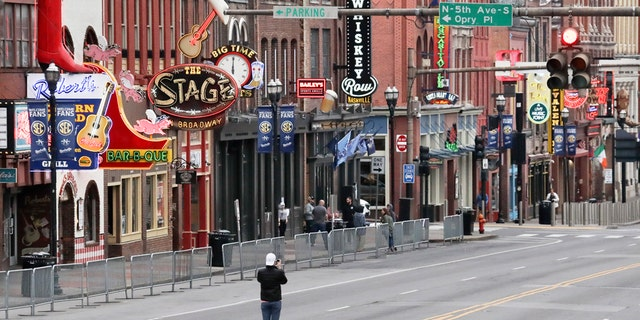 A man stands in the middle of Broadway to take a photo where the streets and sidewalks are normally filled in Nashville, Tenn. on March 23. (AP Photo/Mark Humphrey, File)