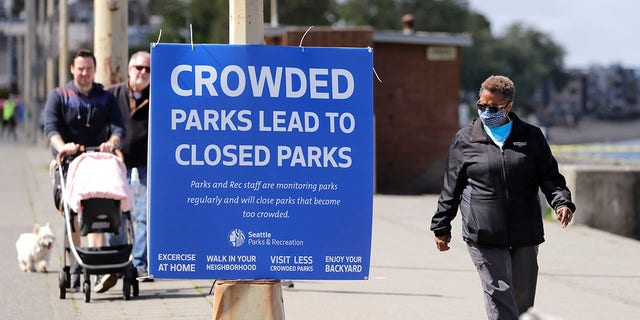 City guidelines for Seattle parks ask that people stay at least 6 feet apart, not to congregate and to keep moving to help prevent spread of the coronavirus. (AP Photo/Elaine Thompson)
