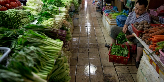 A vendor prepares vegetables for sale at a wet market in Shenzhen, China. (AP Photo/Ng Han Guan)