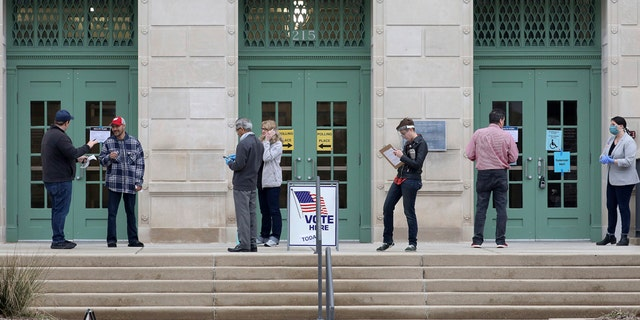 Election workers and voters keep a distance from each other during the state's presidential primary election Tuesday, April 7, 2020 outside the Madison Municipal Building in Madison, Wis. Voters across the state are ignoring a stay-at-home order in the midst of a pandemic to participate in the state's presidential primary election. (John Hart/Wisconsin State Journal via AP)