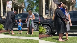 Boy, 3, hands dad MBA diploma during front lawn graduation ceremony