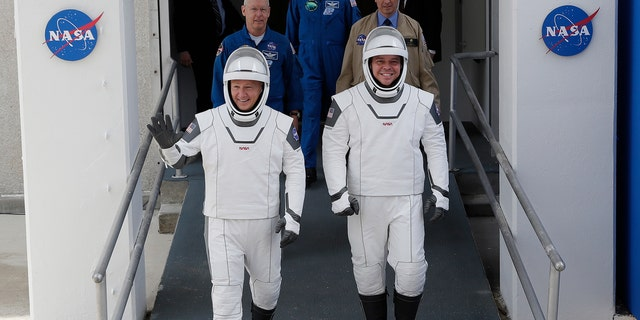 NASA astronauts Douglas Hurley, left, and Robert Behnken wave as they walk out of the Neil A. Armstrong Operations and Checkout Building on their way to Pad 39-A, at the Kennedy Space Center in Cape Canaveral, Fla., Wednesday, May 27, 2020.  (AP Photo/John Raoux)