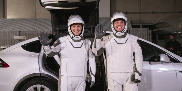 In this Friday, Jan. 17, 2020 photo made available by NASA, astronauts Doug Hurley, left, and Robert Behnken pose in front of a Tesla Model X car during a SpaceX launch dress rehearsal at Kennedy Space Center in Cape Canaveral, Fla. The NASA astronauts rode to the pad in the electric vehicle made by Elon Musk's company.