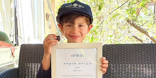 Imri Elya with the ancient tablet and the certificate of recognition given to him by the Israel Antiquities Authority.