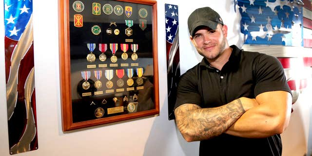 Colin Wayne next to medals he received for combat.