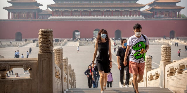 Visitors wearing face masks to protect against the new coronavirus walk through the Forbidden City in Beijing, Friday, May 1, 2020. (Associated Press)