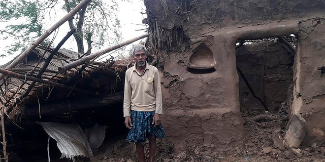 This photo provided by the Indian Red Cross Society shows a villager standing outside his damaged house after Cyclone Amphan, the equivalent of a category 3 hurricane, hit the area in Bhadrak district of Orissa state, May 21. (Indian Red Cross Society via AP)