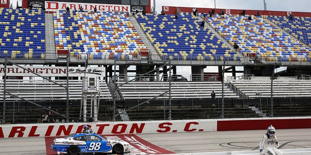 Kyle Busch sits on the pit wall after finishing second to Chase Briscoe (98) in the NASCAR Xfinity series auto race Thursday, May 21, 2020, in Darlington, S.C. (AP Photo/Brynn Anderson)