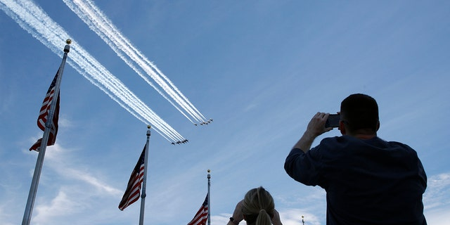 People view the U.S. Navy Blue Angels and U.S. Air Force Thunderbirds from the Washington Monument as they fly over the National Mall in Washington, Saturday, May 2, 2020. The flyover was in salute to first responders in the fight against the coronavirus pandemic. (AP Photo/Patrick Semansky)