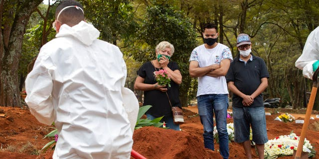 Relatives attend the burial of the remains of a person suspected to have died of COVID-19 disease, at the Vila Formosa cemetery in Sao Paulo, Brazil, Thursday, April 30, 2020.