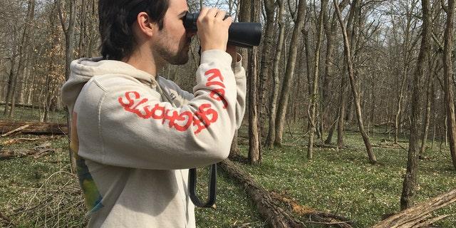 Conner Brown uses binoculars to look for birds in Cedar Island, Maryland.
