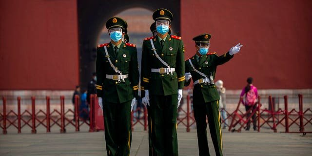 Chinese paramilitary police wear face masks to protect against the spread of the new coronavirus as they stand in formation outside an entrance to the Forbidden City in Beijing, Friday, May 1, 2020. The Forbidden City reopened beginning on Friday, China's May Day holiday, to limited visitors after being closed to the public for more than three months during the coronavirus outbreak. (AP Photo/Mark Schiefelbein)