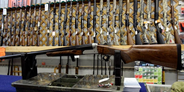 FILE - In a May 16, 2006 file photo, rifles line a hunting store's shelves in Ottawa. Prime Minister Justin Trudeau said Friday, May 1, 2020 that Canada is banning the use and trade of assault-style weapons immediately. (Jonathan Hayward/The Canadian Press via AP)
