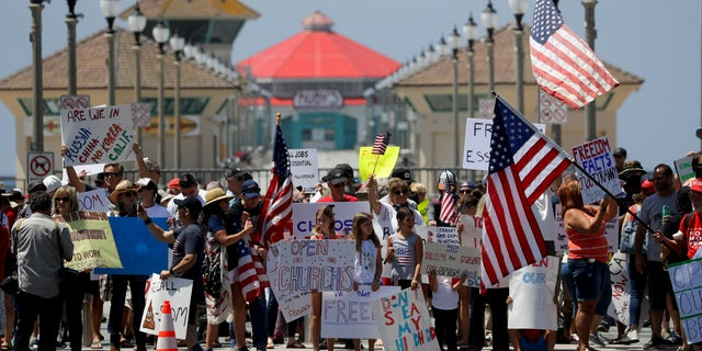 Protesters hold signs and wave flags during a demonstration at the pier Friday, May 1, 2020, in Huntington Beach, Calif., during the coronavirus outbreak. (Associated Press)