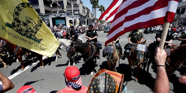 Law enforcement personnel on horseback keep protesters on the sidewalk during a demonstration at the pier Friday, May 1, 2020, in Huntington Beach, Calif., during the coronavirus outbreak. (Associated Press)