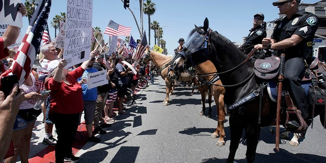 Law-enforcement personnel on horseback keep protesters on the sidewalk during a demonstration at the pier during the coronavirus pandemic Friday, May 1, 2020, in Huntington Beach, Calif. (Associated Press)