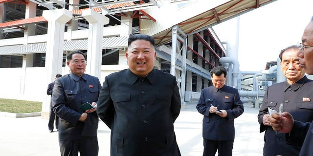 In this Friday, May 1, 2020, photo provided by the North Korean government, North Korean leader Kim Jong Un, center, visits a fertilizer factory in Sunchon, South Pyongan province, near Pyongyang, North Korea.
