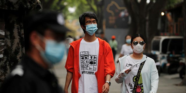 People wearing protective face masks to help curb the spread of the coronavirus, walking through Beijing's popular tourist spot of Nanluonguxiang on Sunday.
