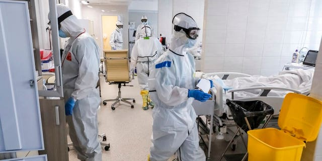 Doctors work inside the intensive care unit for people infected with the new coronavirus, at a hospital in Moscow, Russia.