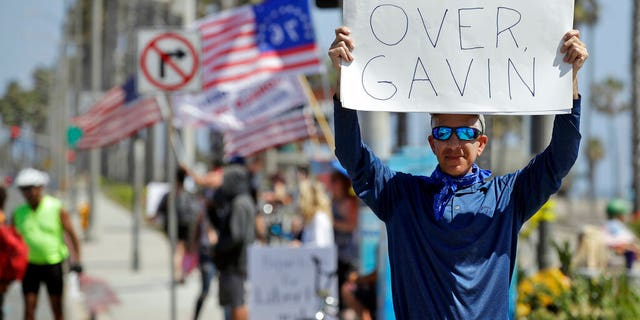 A protester holds a sign in front of the pier Sunday, May 3, 2020, in Huntington Beach, Calif. (Associated Press)