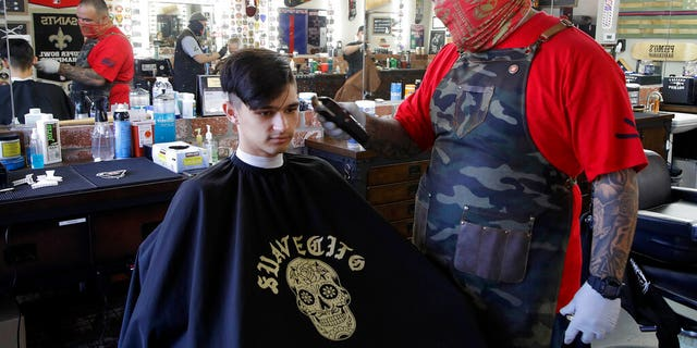 Juan Desmarais, right, the owner of Primo's Barbershop in Vacaville, Calif., on Monday.