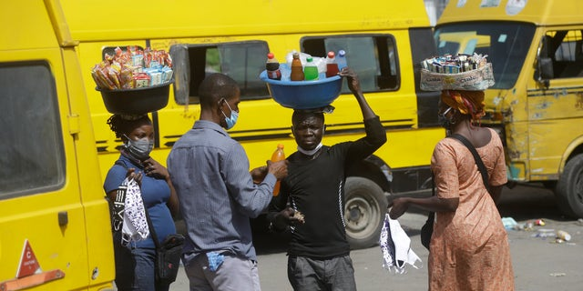 People wearing face masks sells snacks and water to passengers at Obalende bus station in Lagos Nigeria, Tuesday May 5, 2020. Though Nigeria begun a phased easing of its strict lockdown measures on Monday, its confirmed cases of coronavirus continue to increase. (AP Photo/Sunday Alamba)