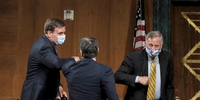 Senate Intelligence Committee Chairman Richard Burr, right, and Vice Chairman Mark Warner, left, greeting Rep. John Ratcliffe at his hearing Tuesday.