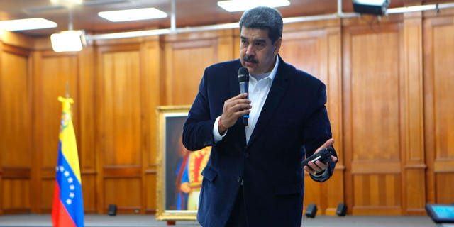 "This photo released by the Venezuelan Miraflores presidential press office shows President Nicolas Maduro speaking over military equipment that he says was seized during an incursion into Venezuela, during his televised address from Miraflores in Caracas, Venezuela, Monday, May 4, 2020. Maduro said authorities arrested two U.S. citizens among a group of ""mercenaries"" on Monday, a day after a beach raid purportedly aimed at capturing the leader that Venezuelan authorities say they foiled. (Miraflores press office via AP)"
