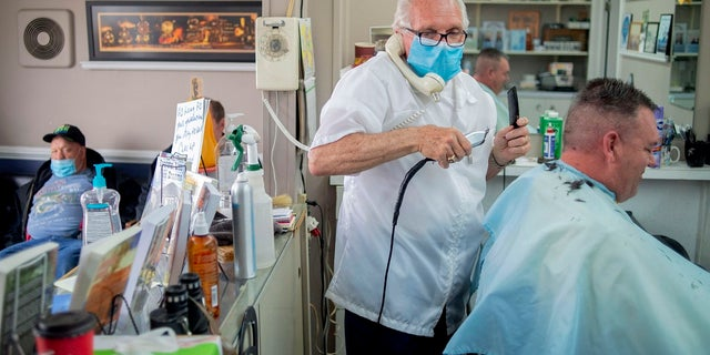 Karl Manke, 77, left, wears a mask while cutting hair on Tuesday at Karl Manke's Barber and Beauty Shop in Owosso, Mich. Manke re-opened his doors on Monday in defiance of Gov. Gretchen Whitmer's executive order mandating salons, barbershops and other businesses to stay closed. (Jake May/The Flint Journal via AP)