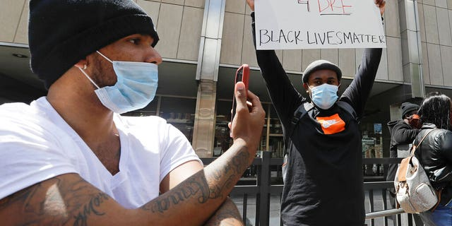 A protester holds a sign outside of the City County Building, Thursday, May 7, 2020, in Indianapolis. The crowd was protesting the fatal shooting Wednesday evening by an Indianapolis Metropolitan Police Officer. (AP Photo/Darron Cummings)