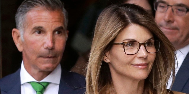 Lori Loughlin, front, and her husband, clothing designer Mossimo Giannulli, left, have entered guilty pleas in the college admissions scandal case. (AP Photo/Steven Senne, File)
