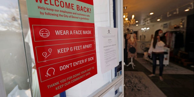 A placard of rules for customers to follow hangs on the door of a boutique as retail businesses are allowed to open their doors to customers for the first time in almost two months with the expiration of the city's stay-at-home order to check the spread of the new coronavirus Saturday, May 9, 2020, in Denver. (AP Photo/David Zalubowski)