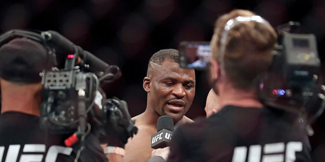 Francis Ngannou, center, is interviewed after winning a UFC 249 mixed martial arts bout against Jairzinho Rozenstruik, Saturday, May 9, 2020, in Jacksonville, Fla. (Associated Press)
