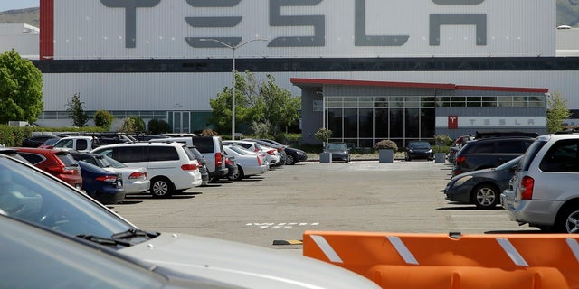 Vehicles are seen parked at the Tesla plant Monday in Fremont, Calif. The parking lot was nearly full at Tesla's California electric car factory Monday, an indication that the company could be resuming production in defiance of an order from county health authorities. (AP Photo/Ben Margot)