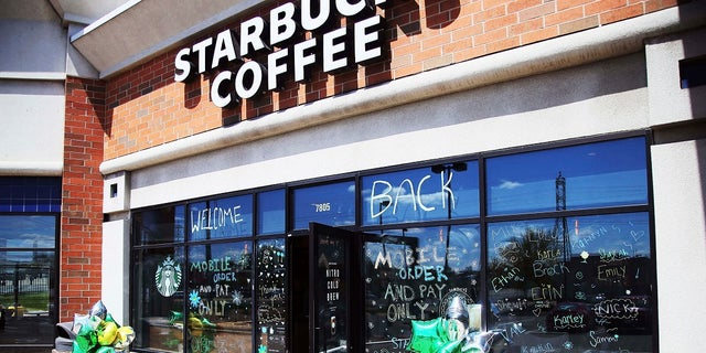 """The Southtown Starbucks Coffee business, which was closed in March and reopened late last week, has a """"WELCOME BACK"""" to customers on the windows Monday in Bloomington, Minn, where customers can pick up their online orders at curbside. (AP Photo/Jim Mone)"""