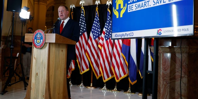 Colorado Gov. Jared Polis makes a point during a news conference to update the state's efforts to check the spread of the new coronavirus on Monday in Denver. Polis announced that a restaurant in Castle Rock, Colo., that opened Sunday in defiance of state rules barring in-person dining will have its business license suspended temporarily for the action. (AP Photo/David Zalubowski)