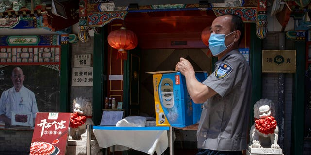 A security guard carries supplies past a reopened restaurant in Beijing Tuesday, May 12, 2020.