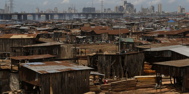 People from a slum work in a sawmill overlooking Lagos downtown in Nigeria, Tuesday May 12, 2020. Though Nigeria began a phased easing of its strict lockdown measures on May 4, its confirmed cases of coronavirus continue to increase. (AP Photo/Sunday Alamba)