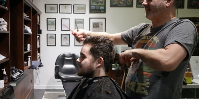 Cathedral Junction Barbers owner Conrad Fitz-Gerald cuts the hair of his son Heathcliff just past midnight in Christchurch, New Zealand. (AP Photo/Mark Baker)