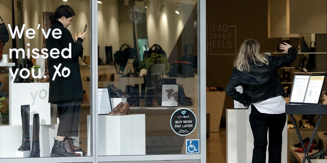A customer gestures as she walks into a store in Christchurch, New Zealand, May 14. New Zealand lifted most of its remaining lockdown restrictions from midnight Wednesday as the country prepares for a new normal. Malls, retail stores and restaurants will reopen and many people will return to their workplaces. (AP Photo/Mark Baker)