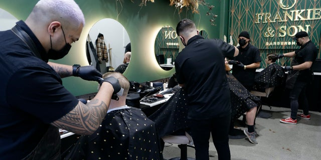 Barbers cut customers' hair in Christchurch, New Zealand, Thursday, May 14, 2020. (AP Photo/Mark Baker)