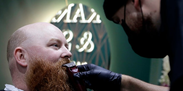 A man has his beard trimmed at a barbers in Christchurch, New Zealand, May 14. New Zealand lifted most of its remaining lockdown restrictions from midnight Wednesday (noon Wed GMT) as the country prepares for a new normal. Malls, retail stores and restaurants will reopen and many people will return to their workplaces. (AP Photo/Mark Baker)