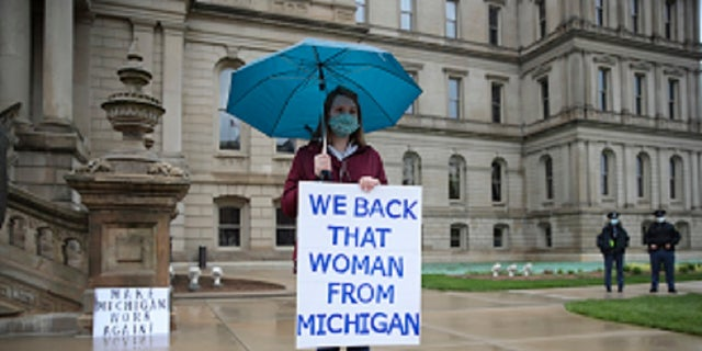 A counter protester holds a sign supporting Michigan Gov. Gretchen Whitmer's stay-at-home order during a rally at the State Capitol in Lansing, Mich., Thursday. (AP Photo/Paul Sancya)