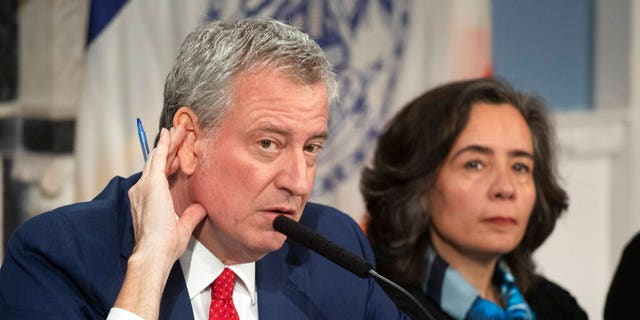 Mayor Bill de Blasio, left, with Dr. Oxiris Barbot, commissioner of the New York City Department of Health and Mental Hygiene, listens to a reporter's question in New York on Feb. 26, 2020. (AP Photo/Mark Lennihan, File)