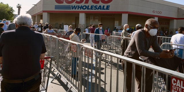 Customers wearing protective masks from the coronavirus and keeping social distancing space line up to enter a Costco Wholesale store in the Van Nuys section of Los Angeles on Saturday. (AP Photo/Richard Vogel)