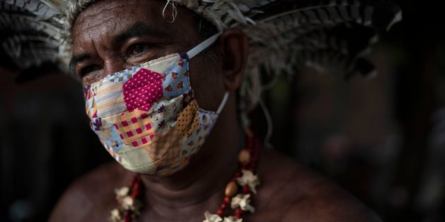Pedro dos Santos, the leader of a community named Park of Indigenous Nations, poses for a photo, in Manaus, Brazil this May. Manaus' lack of the new coronavirus treatment prompted Pedro dos Santos to drink tea made of chicory root, garlic and lime to combat a high fever that lasted 10 days. (AP Photo/Felipe Dana)