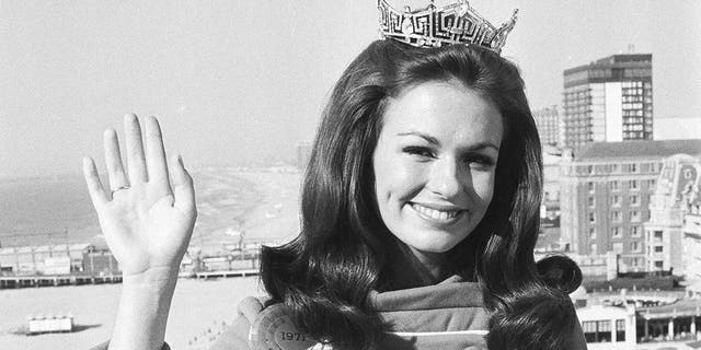 Phyllis George of Denton, Texas, the 21-year-old newly crowned Miss America, waves against backdrop of the beach and ocean at Atlantic City, N.J., Sept. 13, 1970. (Associated Press)